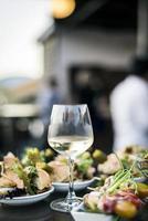 bicchiere di vino bianco con cibo gourmet tapas snack nel bar all'aperto al tramonto foto
