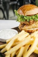hamburger di filetto di pesce con patatine fritte e salsa tartara set snack pasto foto