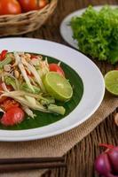 insalata di papaya su un piatto bianco su un tavolo di legno foto