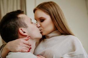 ritratto ravvicinato di una bellissima giovane coppia che si bacia a letto a casa foto