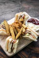 classico club sandwich gourmet con patatine fritte su tavola di legno foto