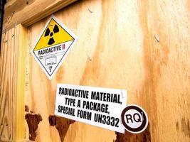 etichetta radiazioni accanto alla scatola di legno per il trasporto digitare un pacco foto