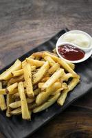 Spuntino laterale delle patatine fritte con salse di immersione sul tavolo di legno foto