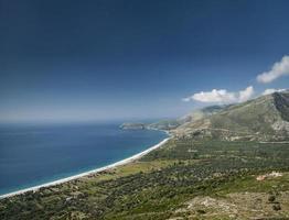 Paesaggio della spiaggia della costa del mar mediterraneo ionico dell'albania meridionale a nord di sarande sulla strada per vlore foto
