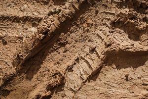 consistenza del terreno umido e appiccicoso con tracce delle ruote delle auto foto