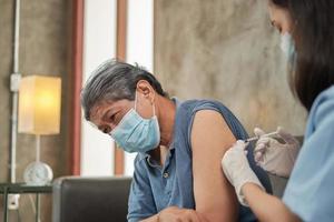 una dottoressa asiatica sta vaccinando un uomo anziano a casa. foto