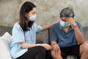 medico con maschera facciale che controlla la salute del paziente a casa. foto