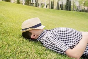giovane uomo premuroso seduto sull'erba nel parco foto