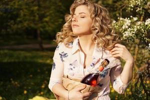 bella giovane donna con in mano una bottiglia di vino vuota foto
