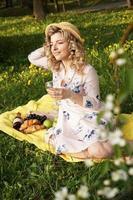 bella giovane donna con capelli biondi in cappello di paglia beve vino foto
