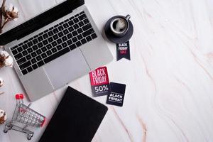 parole di vendita del venerdì nero sull'etichetta, area di lavoro con laptop, notebook foto