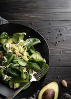 vista dall'alto di avocado fresco estivo e insalata di spinaci su legno nero foto