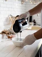 Mani maschili sbattere gli albumi e lo zucchero semolato su legno bianco foto