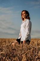 felice giovane donna in una camicia bianca in un campo di grano. giorno soleggiato. foto