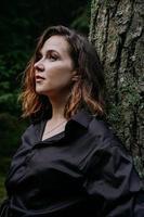 giovane donna - chiudere il ritratto in una foresta oscura. donna in camicia nera foto