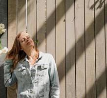 giovane donna in piedi in rose bianche in un giardino o in un parco foto
