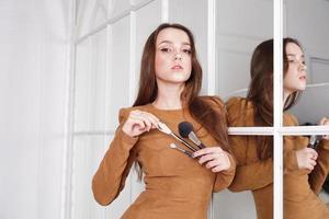 truccatore con in mano un pennello da cipria, riflesso nello specchio foto