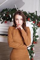 ragazza vicino a un pianoforte a coda bianco con decorazioni natalizie foto