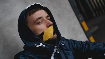 uomo con del nastro adesivo sulla bocca foto