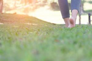 donna a piedi nudi che cammina sull'erba verde nel parco? foto
