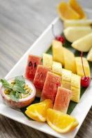 piatto misto di macedonia di frutta biologica tagliata fresca all'aperto su tavola di legno foto