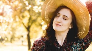 ritratto, bella giovane donna che indossa un cappello di paglia all'ora del tramonto foto