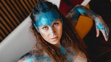 donna con scintillii sul viso. ragazza con trucco artistico foto