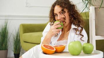 donna che mangia mela verde a casa. alimentazione sana, concetto di cibo dietetico foto