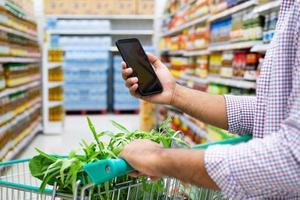 giovane che utilizza smartphone durante lo shopping al supermercato. foto
