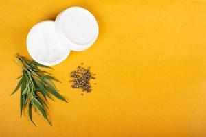 crema di semi di canapa su sfondo giallo bellezza cura della pelle. foto