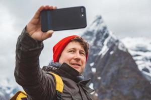 uomo che si fa un selfie con le montagne alle spalle foto