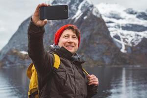 uomo che si fa selfie con montagne e lago dietro di lui foto