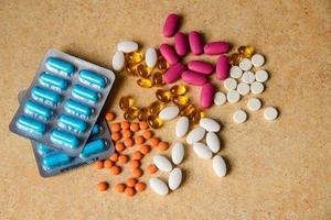 blister con pillole blu, rosa e arancioni, vitamine, capsule di olio di pesce foto
