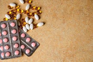 blister con compresse rosa e vitamina d e capsule con olio di pesce giacciono caoticamente sullo sfondo di un piano di lavoro di sabbia foto