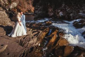 coppia sposata che si abbraccia con uno sfondo di montagna e fiume foto