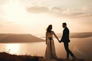 coppia sposata che si abbraccia su una montagna foto