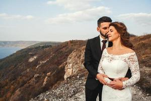 coppia sposata che si tiene per mano su una montagna foto