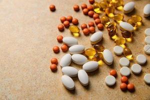 pillole d'arancia, vitamina d e capsule di olio di pesce giacciono casualmente contro un piano di lavoro di sabbia foto