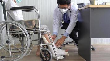 dottore che esamina una gamba rotta foto