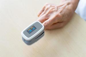 paziente con pulsossimetro al dito foto
