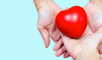 mani che tengono un cuore foto