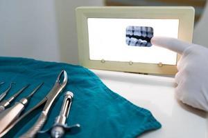 dentista che mostra i raggi x del paziente in clinica odontoiatrica foto