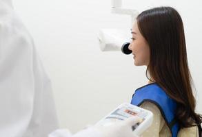 dentista che utilizza una macchina a raggi X per scansionare il dente del paziente in clinica foto
