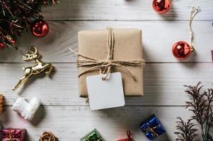 confezione regalo con un piccolo regalo su uno sfondo di legno bianco foto