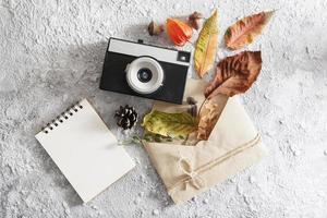 layout piatto autunnale con macchina fotografica vintage, busta foto