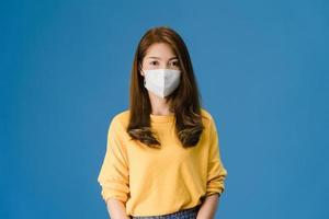 giovane ragazza asiatica che indossa maschera medica su sfondo blu. foto