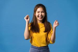 giovane signora asiatica gioiosa ed emozionante su sfondo blu. foto