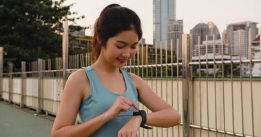 la signora dell'atleta dell'asia si esercita guardando il cardiofrequenzimetro su smartwatch. foto