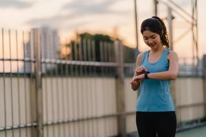 la signora dell'atleta dell'asia si esercita controllando il cardiofrequenzimetro su smartwatch. foto