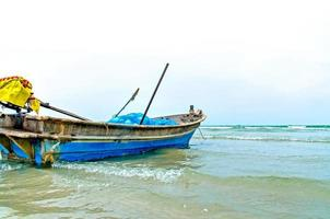 la spiaggia di sabbia e mare con barca parcheggiata sul lungomare. foto
